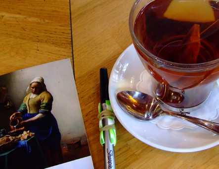 A cup of tea with a journal and a pen